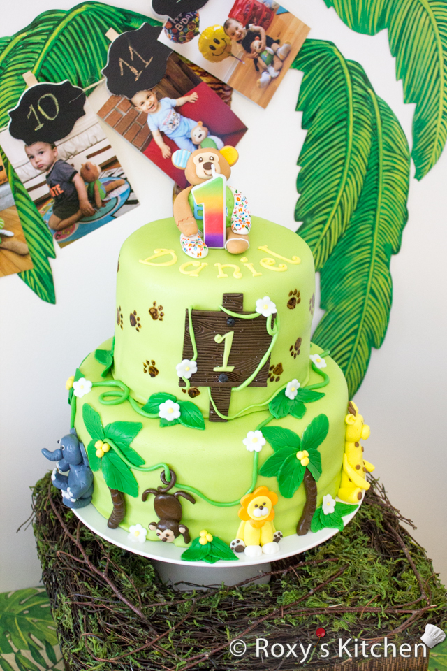 Safari / Jungle Themed First Birthday Party - Dessert Ideas: Two-tier Jungle Animals Birthday Cake. It's a chocolate & walnut cake covered in fondant and decorated with fondant leaves and animals - lion, monkey, giraffe, elephant