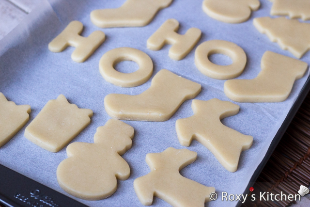 Christmas Sugar Cookies Covered with Modeling Chocolate - On a lightly floured surface roll the dough until it's about ¼ inches thick. Using the cookie cutters, cut out the dough and place the cookies in a baking pan lined with parchment paper.